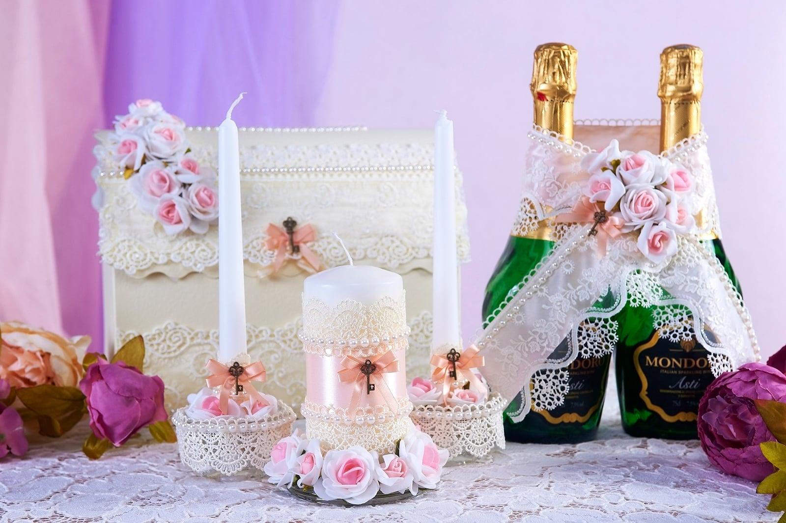 Свадебные свечи с кружевным декором и розовыми атласными лентами.