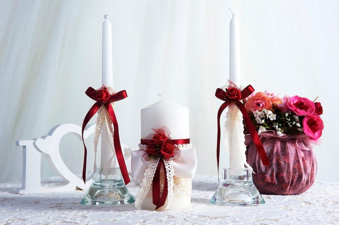 Свадебные свечи, оформленные бордовыми атласными лентами.