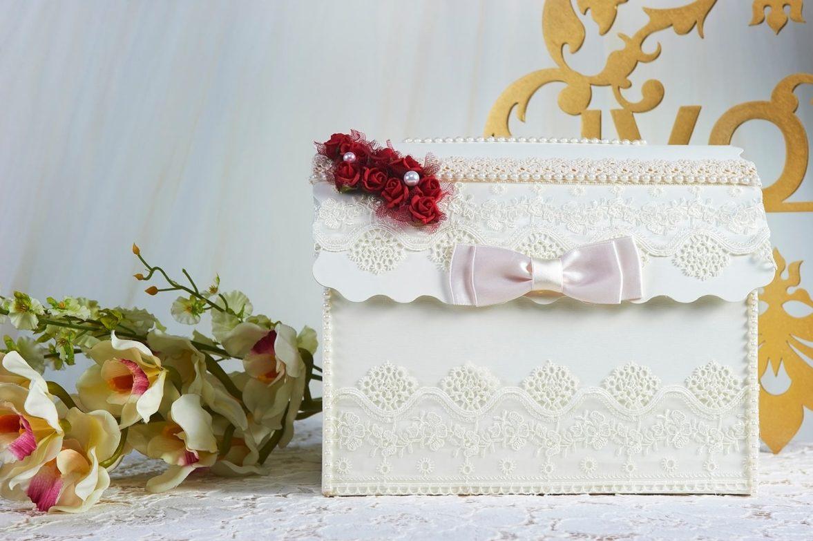 Романтичная свадебная корзинка, украшенная кружевом и красными бутонами.