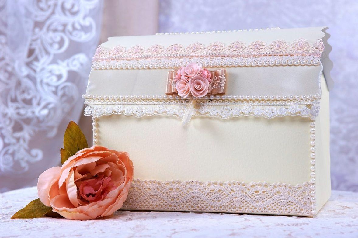 Кремовая свадебная корзинка, украшенная кружевом и розовыми бутонами.