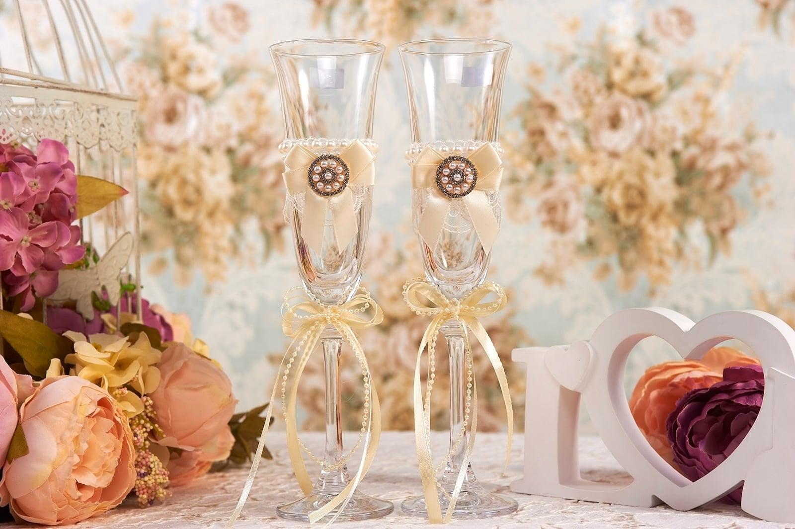 Прозрачные свадебные фужеры, оформленные золотистым атласом.