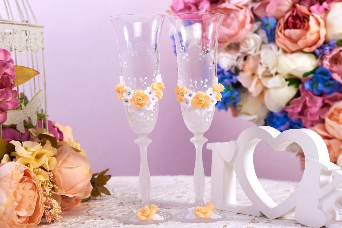 Свадебные фужеры, украшенные золотистыми бутонами и белым узором.