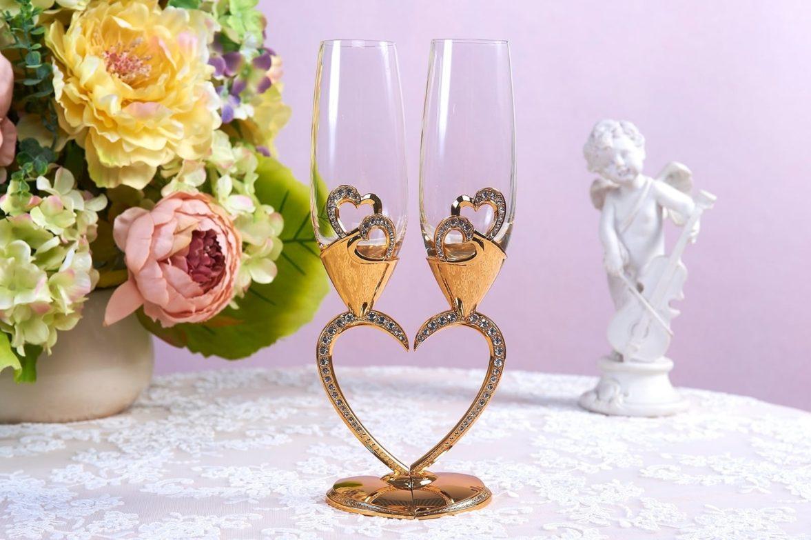 Прозрачные свадебные фужеры с золотистыми ножками в форме сердца.