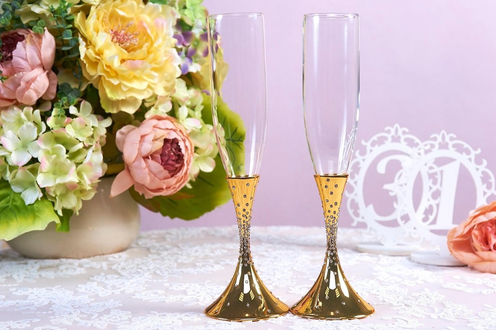 Прозрачные свадебные фужеры с золотистыми ножками.