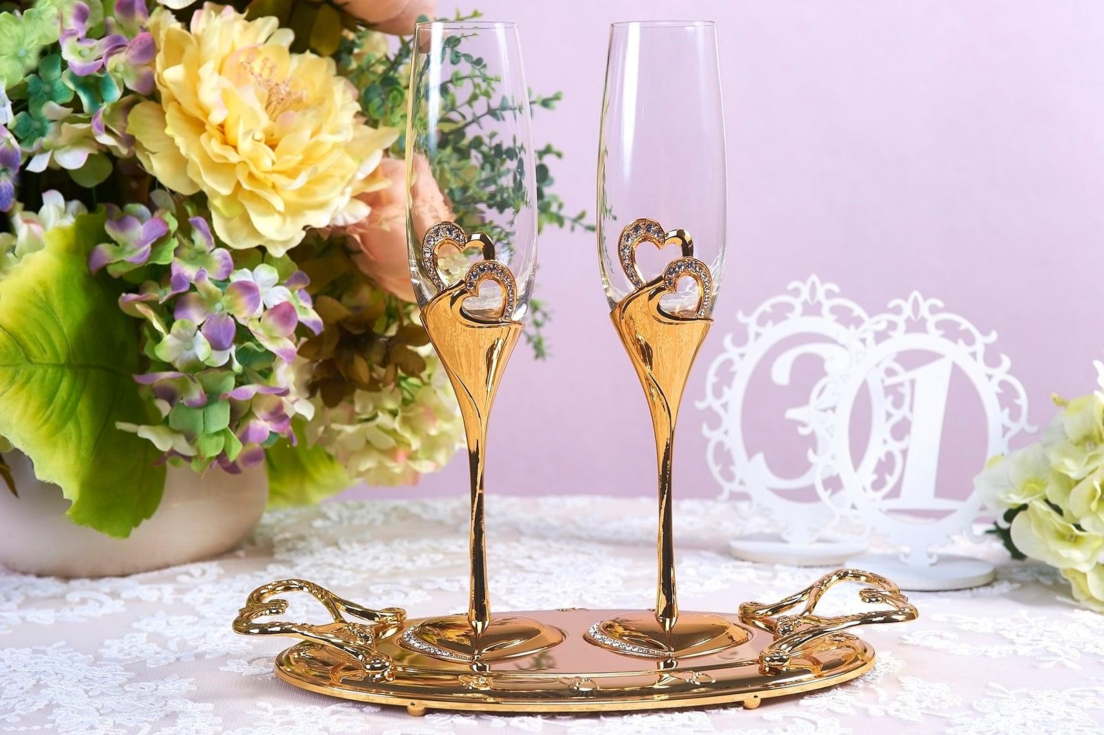 Прозрачные свадебные фужеры с золотыми ножками и сердцами.