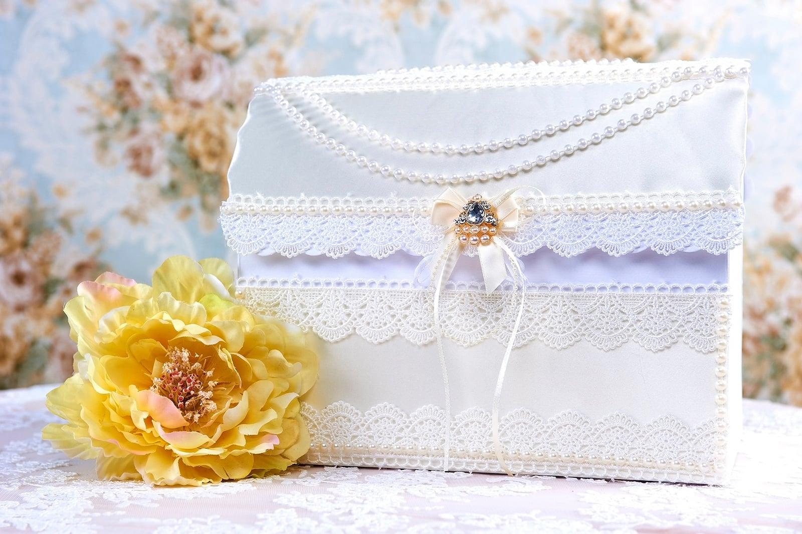 Белая кружевная свадебная корзинка с отделкой в кремовых тонах.
