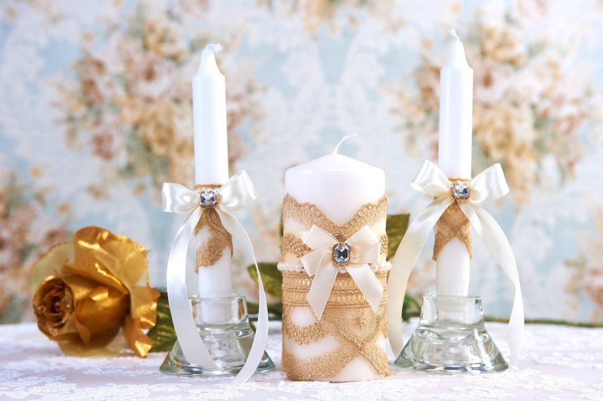 Белые свадебные свечи, декорированные золотистыми лентами.