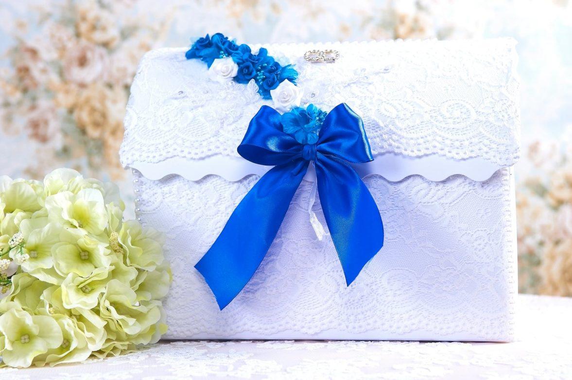Белая кружевная свадебная корзинка с синим атласным бантом.