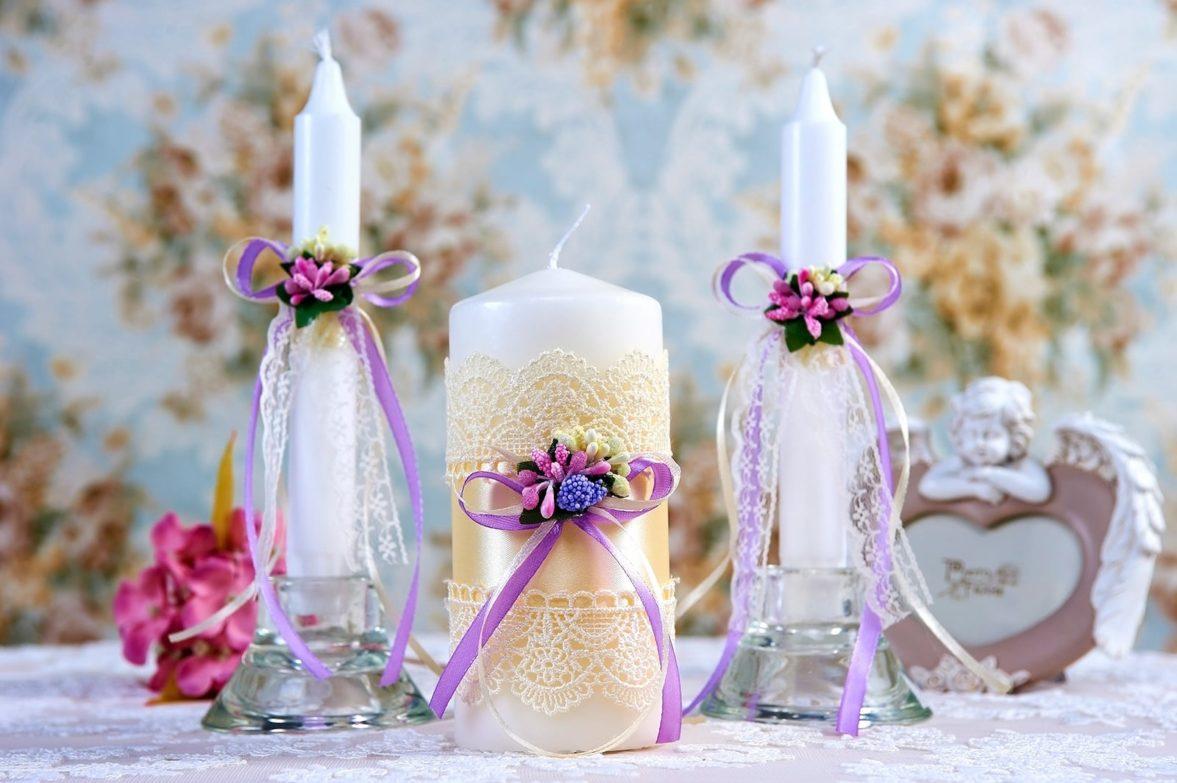 Свадебные свечи с отделкой золотистой лентой и лавандовыми бантами.