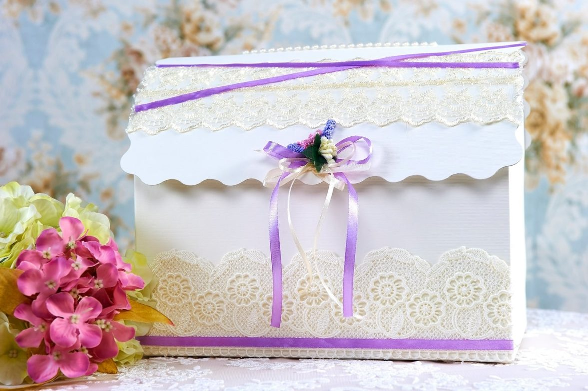 Свадебная корзинка, украшенная белым кружевом и сиреневой лентой.