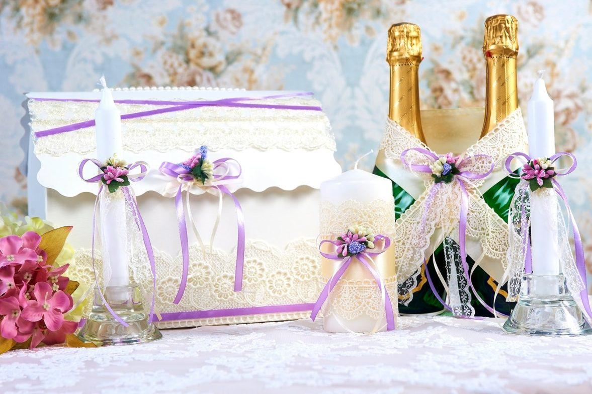 Свадебный набор, декорированный кремовым кружевом и сиреневыми лентами.