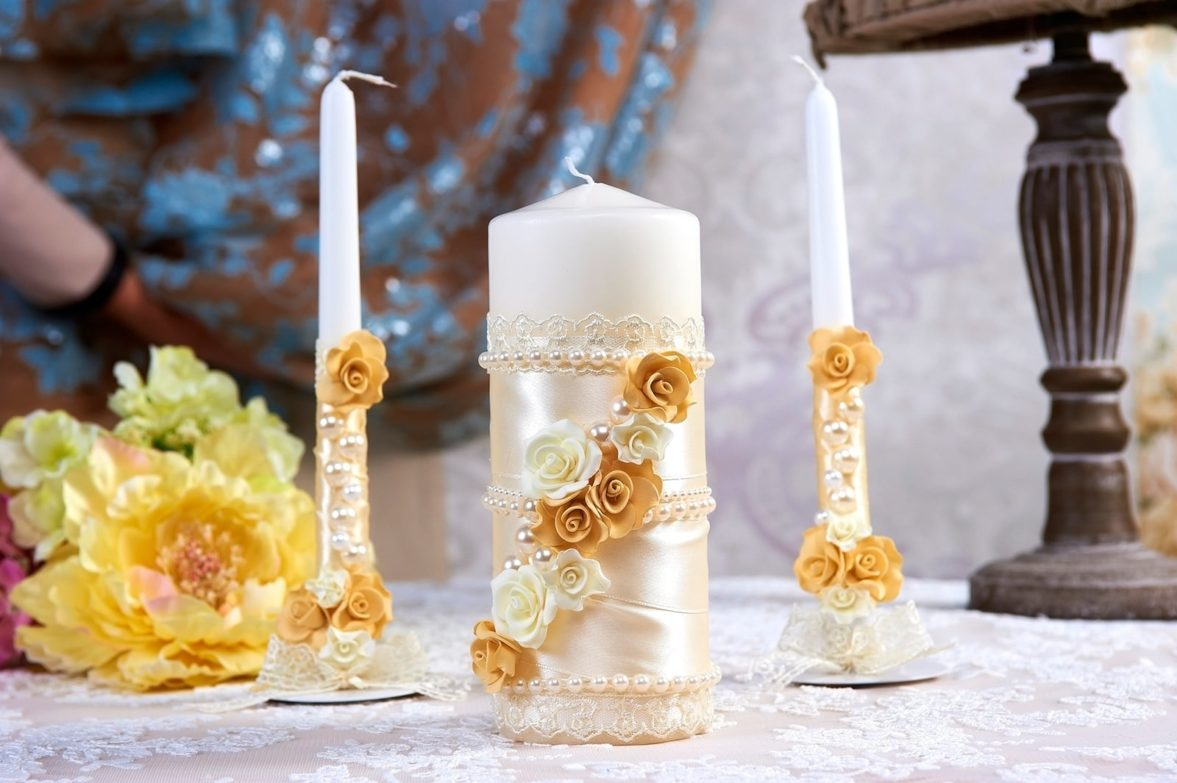 Белые свадебные свечи с золотистым декором из лент, бусин и бутонов.