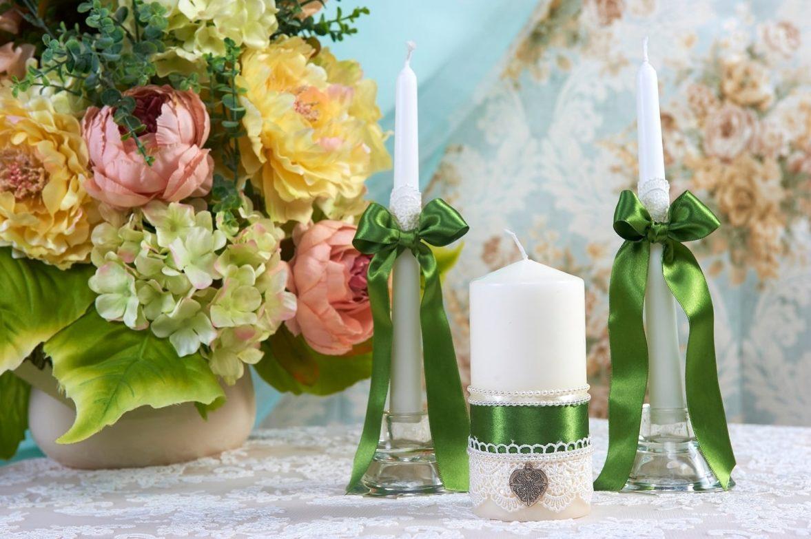 Свадебные свечи с зелеными атласными лентами и белым кружевом.