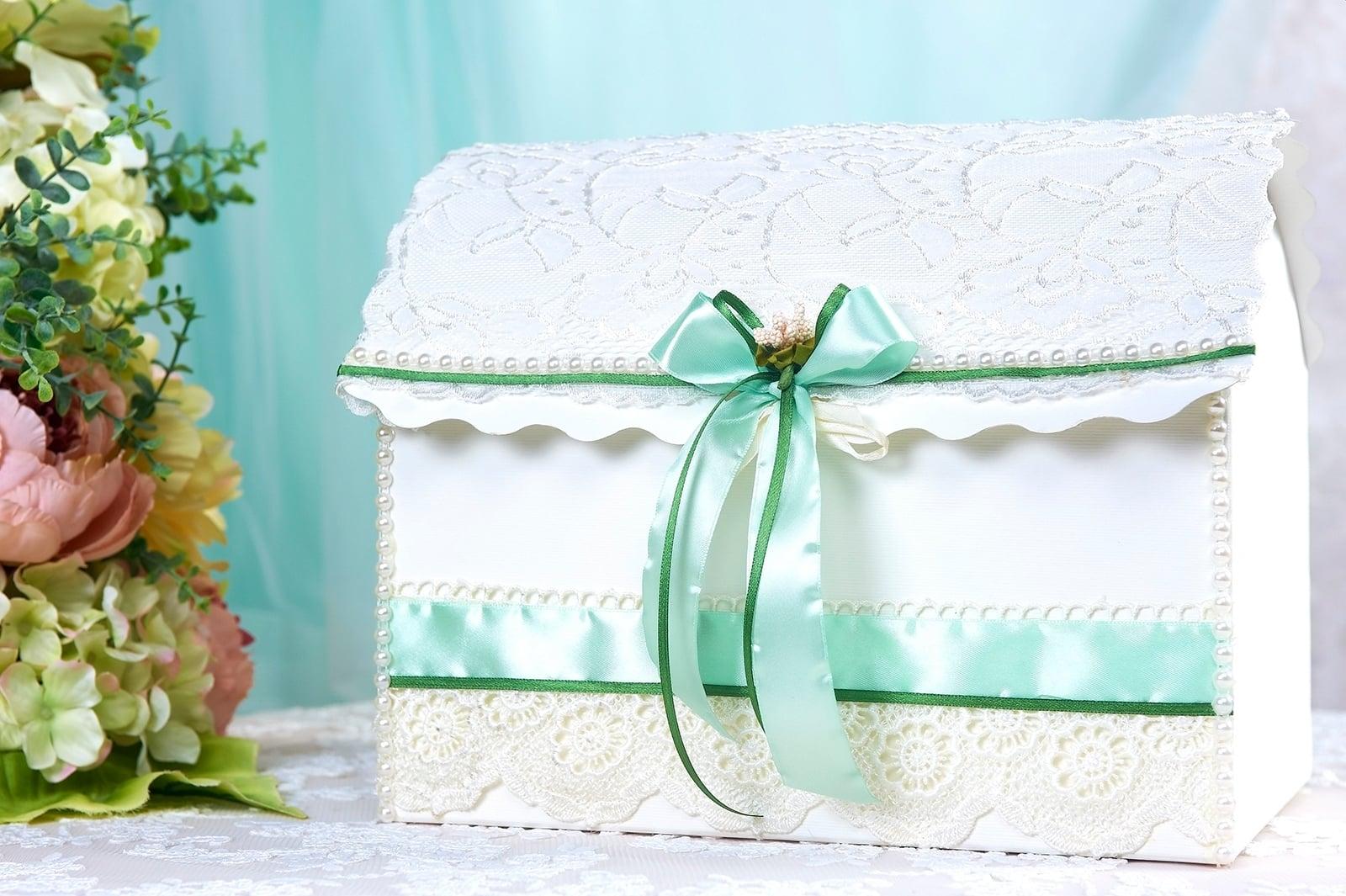 Белая свадебная корзинка, украшенная кружевом и салатовой лентой.