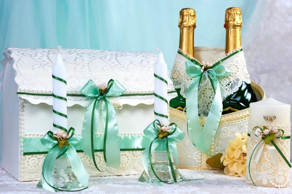 Кружевной свадебный набор, украшенный салатовыми лентами.
