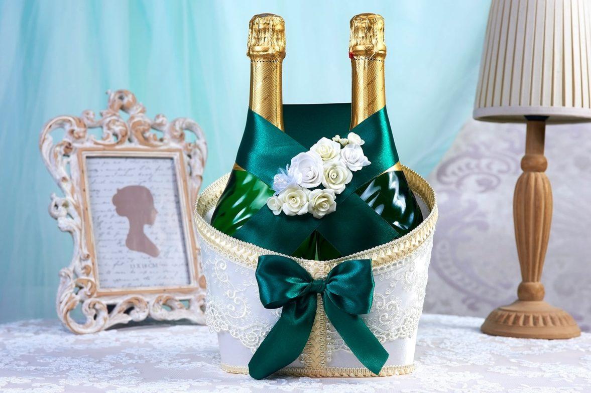 Декор для шампанского с изумрудной лентой и белыми бутонами.