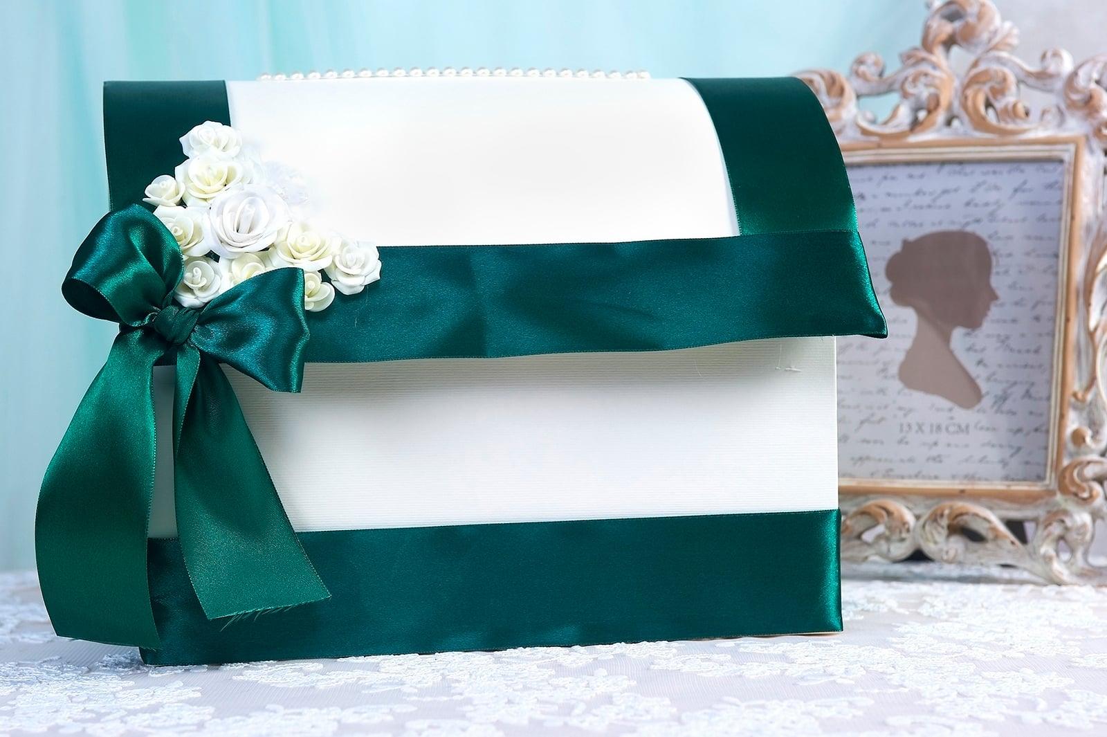 Свадебная корзинка белого цвета, украшенная изумрудной лентой.