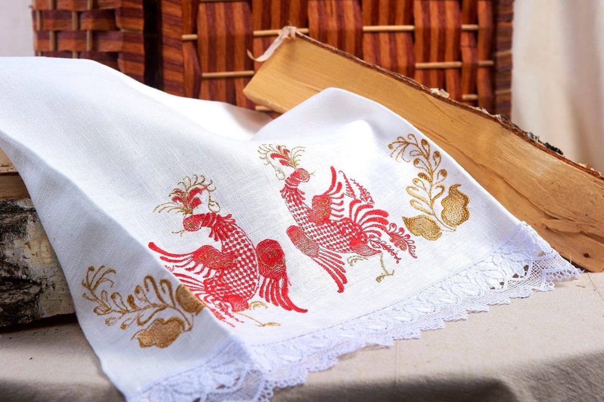 Белый свадебный рушник, украшенный красно-золотистой вышивкой.