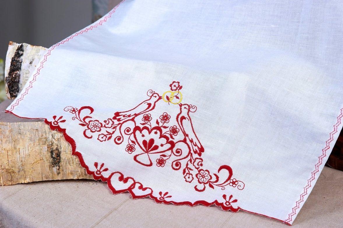 Белый свадебный рушник, украшенный яркой красной вышивкой.