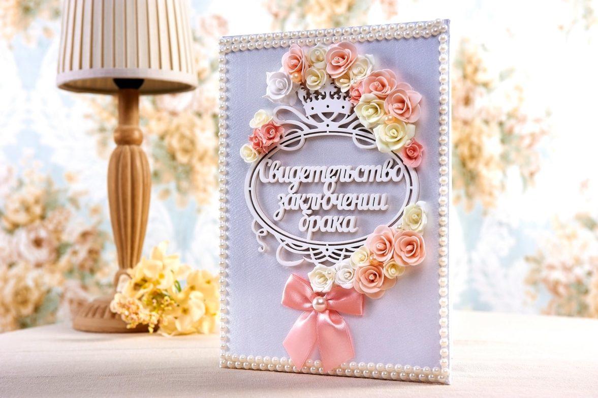 Белая папка для свидетельства о браке, украшенная кремовыми цветами.