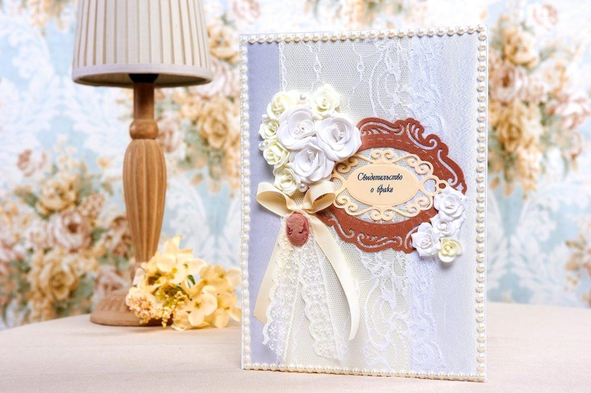 Белая атласная папка для свидетельства о браке, украшенная кружевом и лентами.