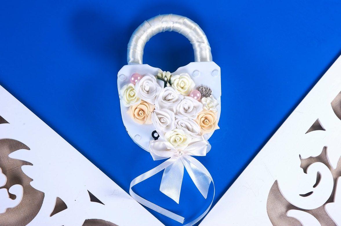 Белый свадебный замок, декорированный атласом и бутонами.