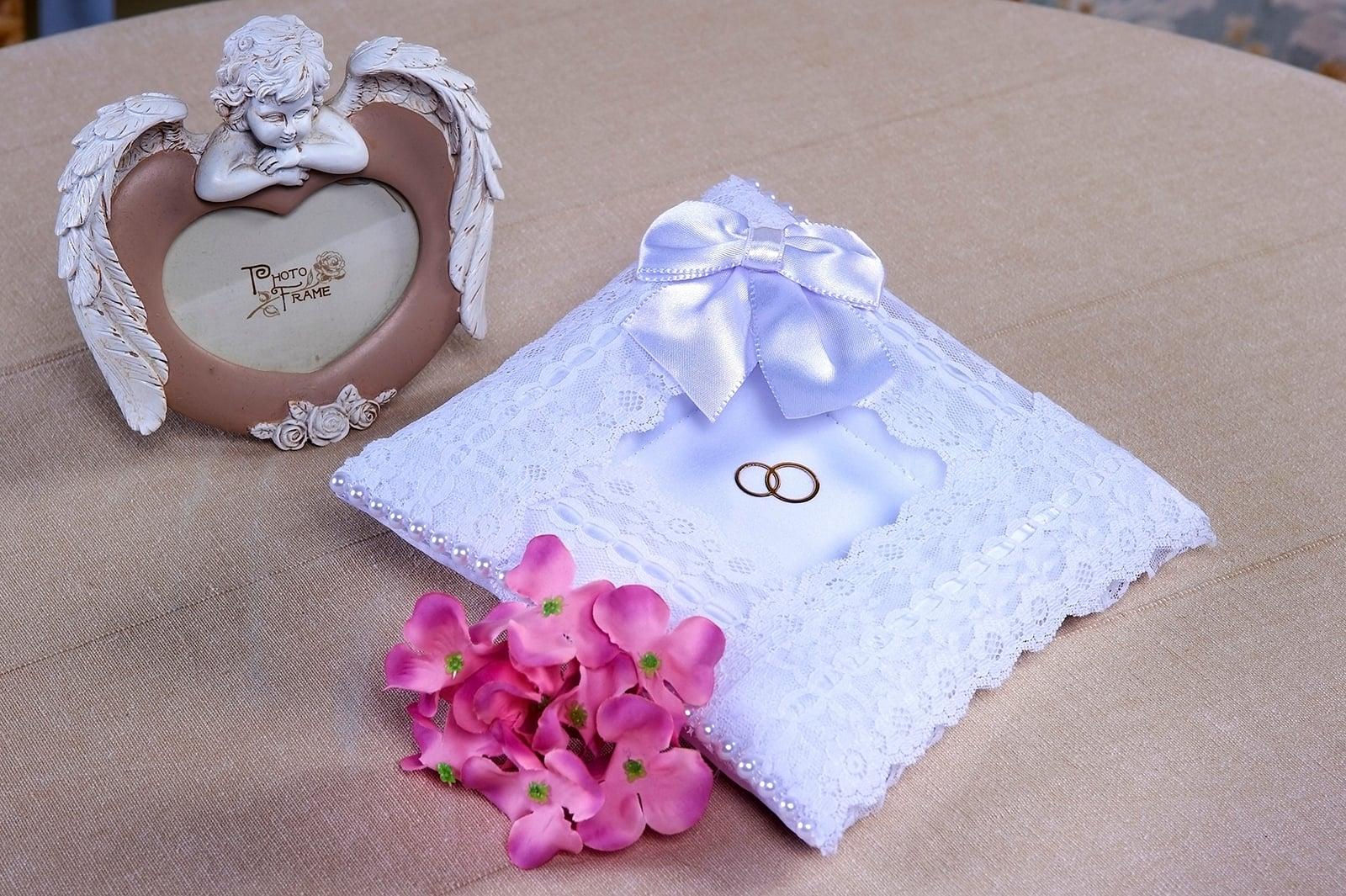 Белая кружевная подушечка для колец, украшенная атласным бантом.