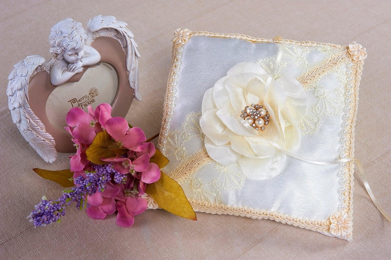 Белая подушечка для колец с кремовой отделкой и пышным бутоном.