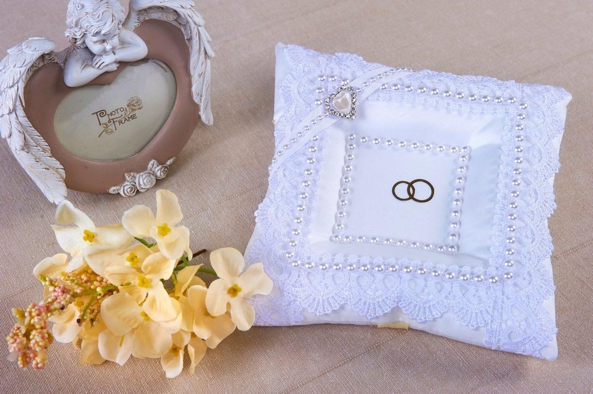 Кружевная белая подушечка для колец с сияющим серебристым декором.