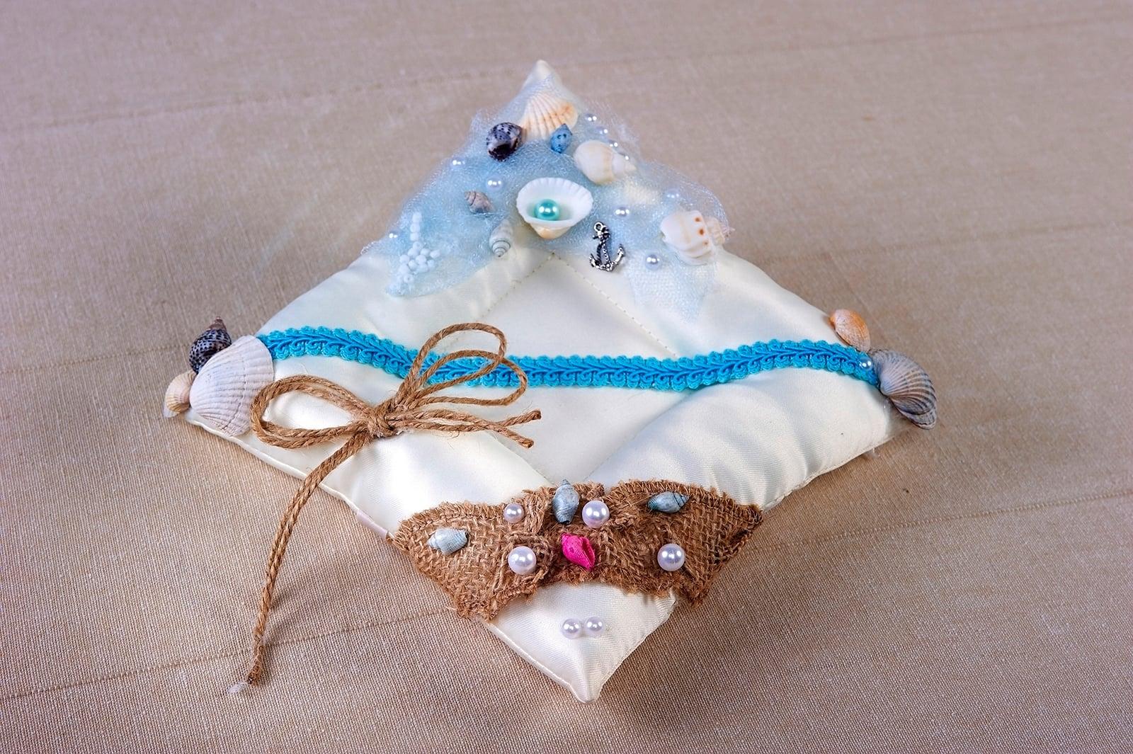 Бежевая подушечка для колец с романтичным цветным декором.