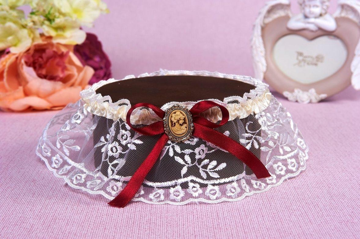 Полупрозрачная кружевная подвязка, декорированная бордовым бантом.