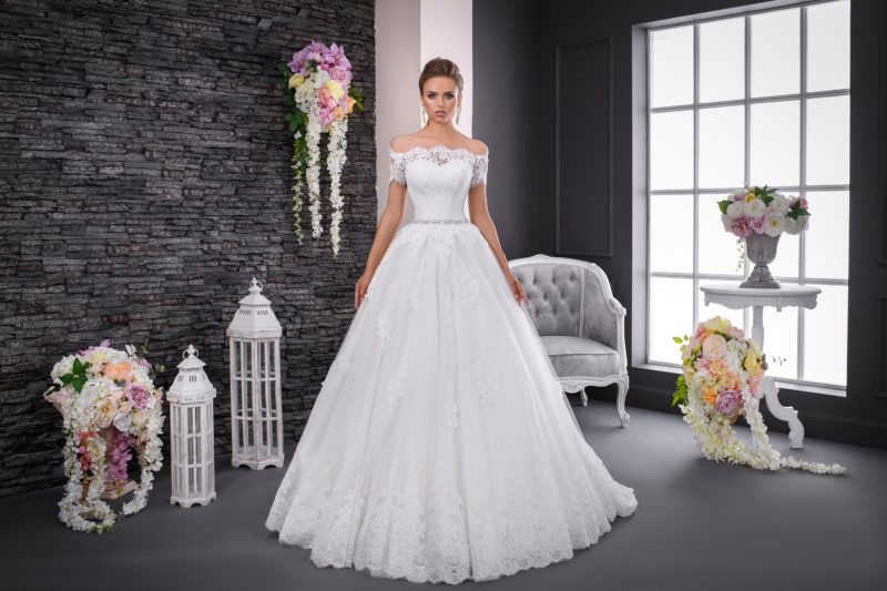 Пышное свадебное платье с фигурным портретным вырезом, коротким рукавом и узким поясом.