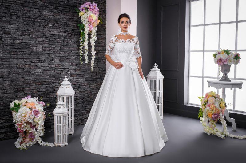 Атласное свадебное платье пышного кроя с бантом на талии и кружевным рукавом.