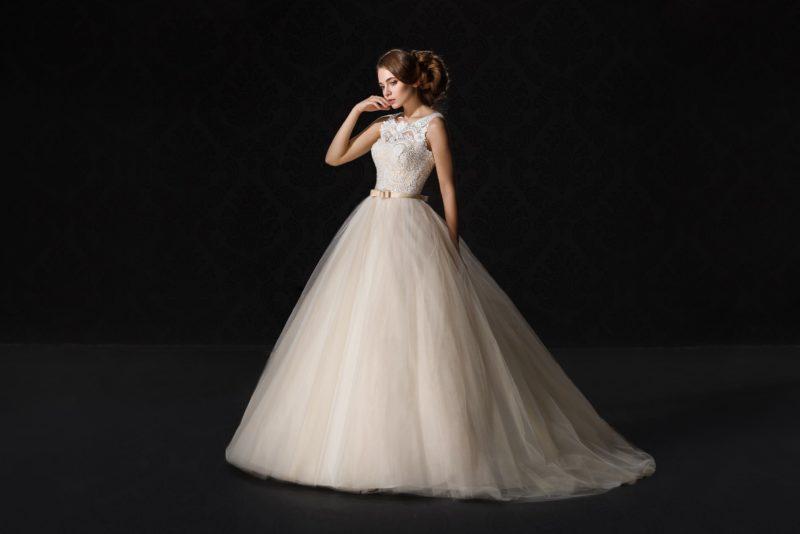 Бежевое свадебное платье пышного кроя с закрытым кружевным верхом.