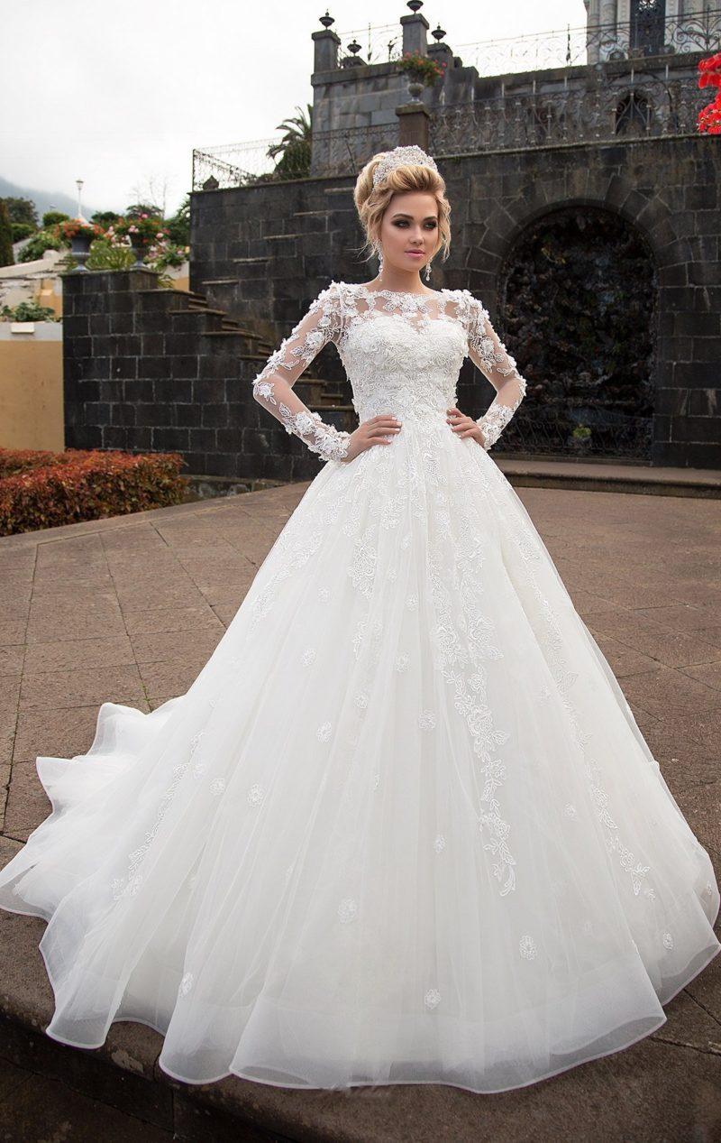 Пышное свадебное платье с длинным шлейфом и съемным верхом с длинными рукавами.