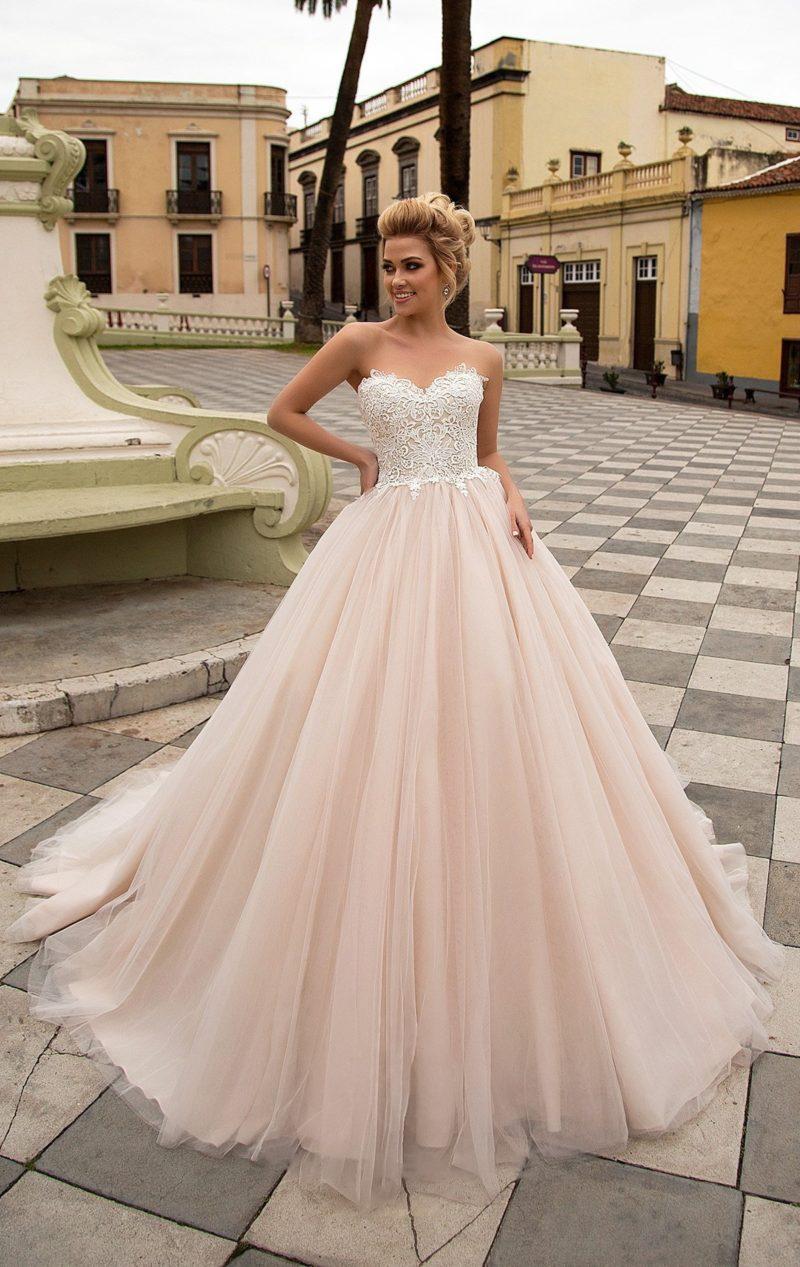 Пудровое свадебное платье с роскошной многослойной юбкой и открытым корсетом с кружевом.