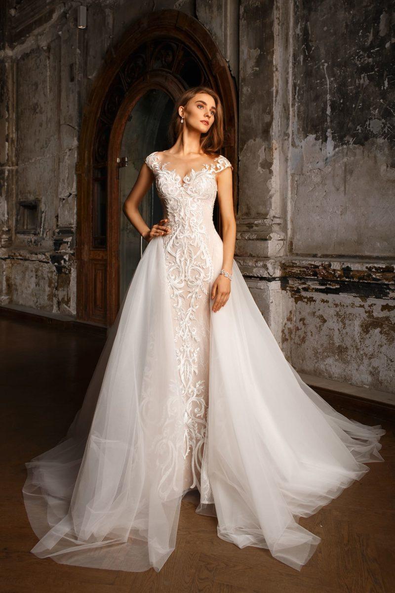Кремовое свадебное платье облегающего кроя с пышной верхней юбкой из белого фатина.