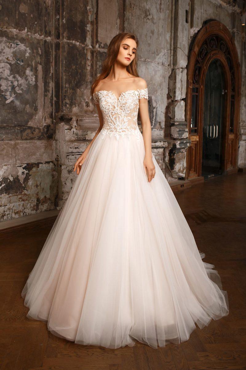 Пышное свадебное платье с изящным открытым декольте и кружевной отделкой корсета.