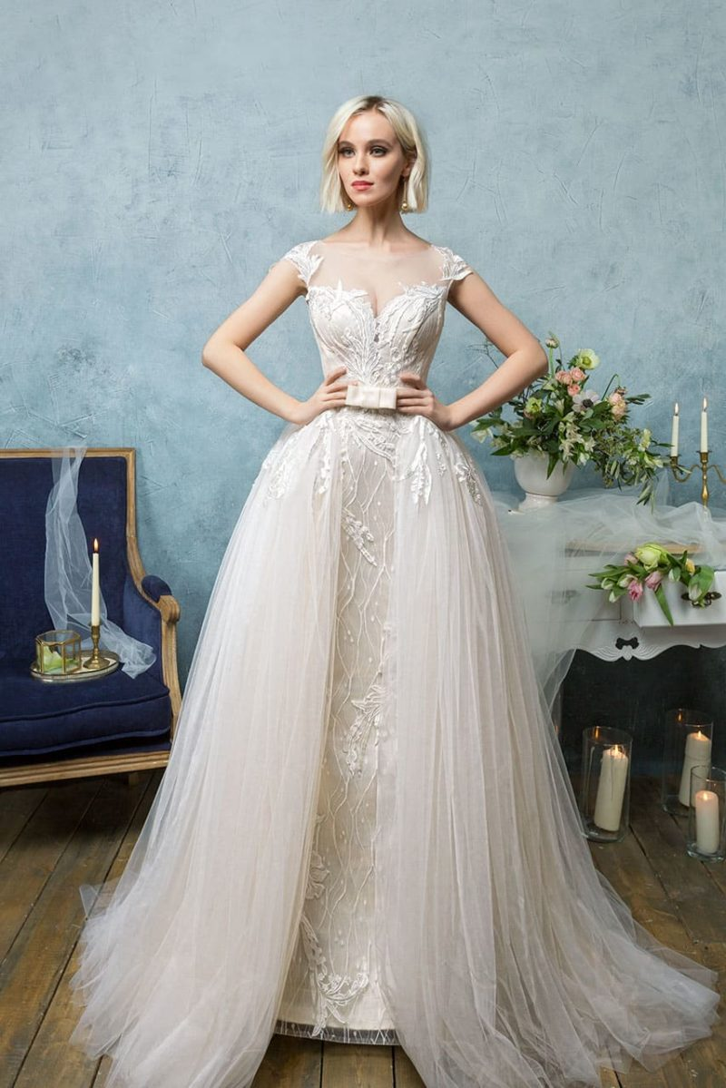 Свадебное платье с пышной верхней юбкой, атласным поясом и роскошной вышивкой.