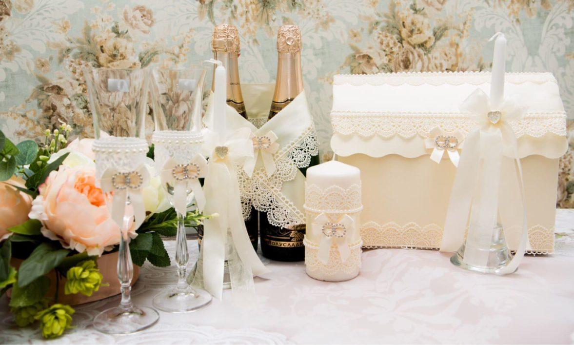 Элегантный свадебный набор в кремовых тонах, оформленный кружевом и лентами.