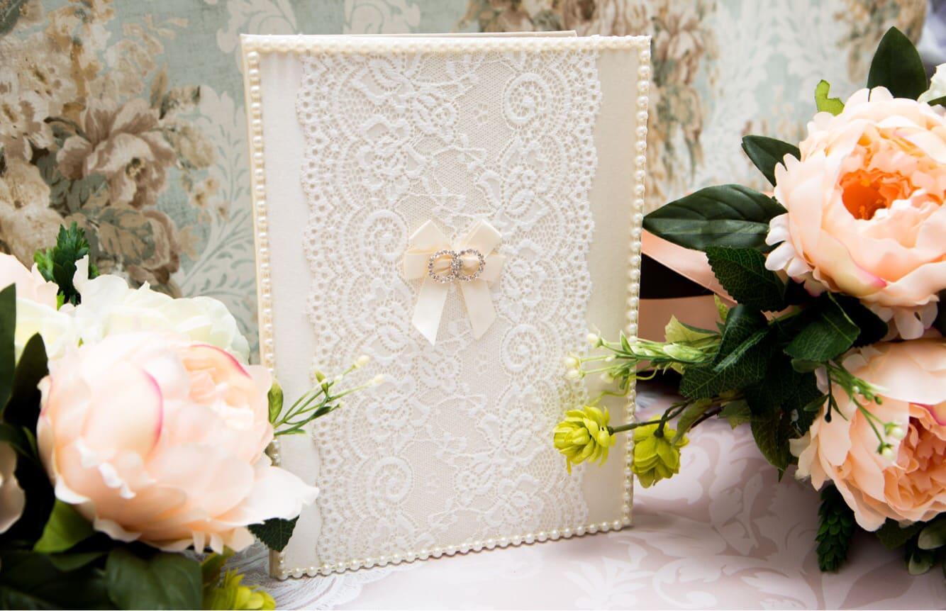 Кремовая папка для свидетельства о браке, покрытая кружевом и украшенная жемчугом.
