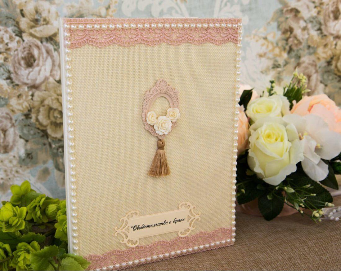 Розовая папка для свидетельства о браке, украшенная кружевной тесьмой и жемчугом.