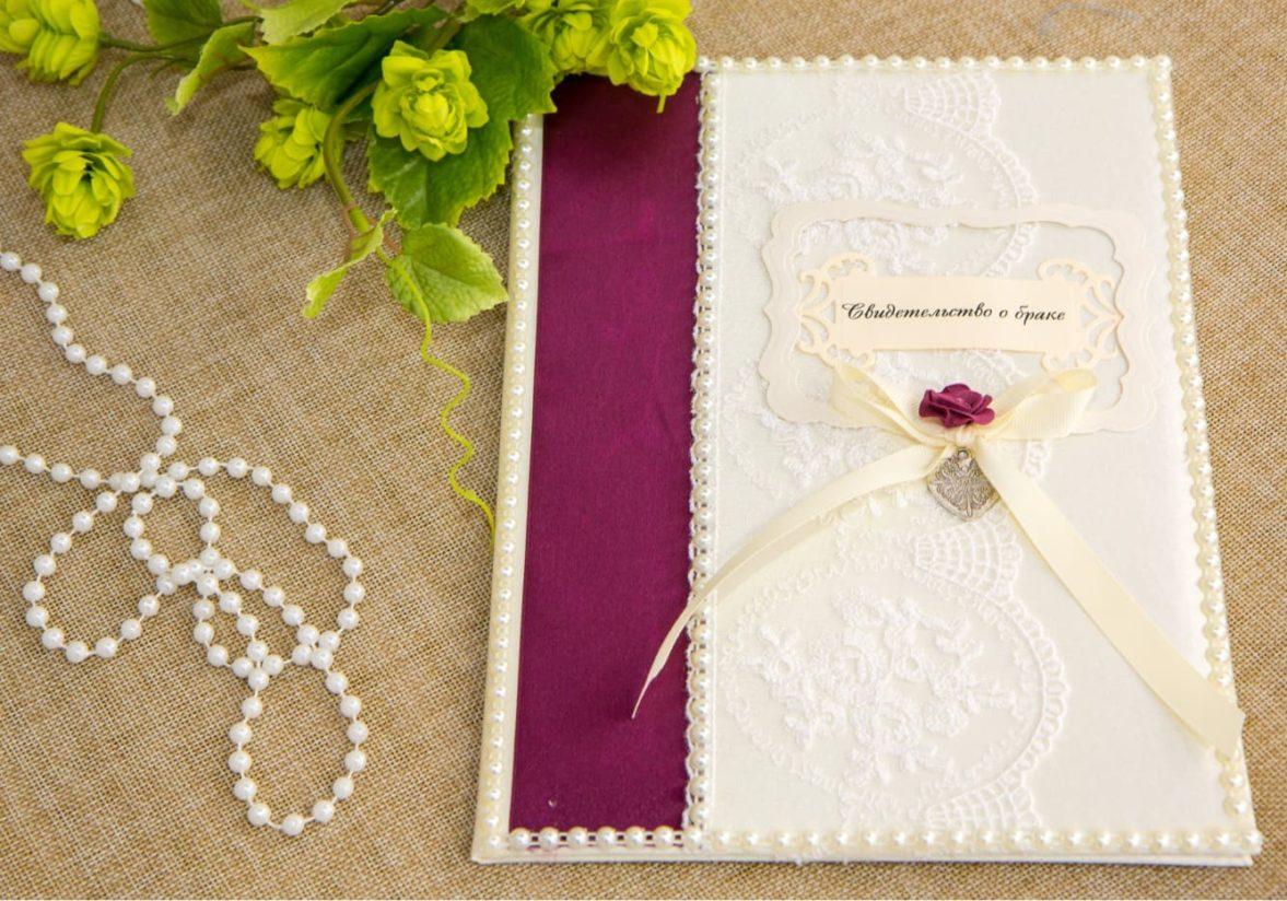 Кружевная папка для свидетельства, оформленная бордовым декором и бутонами.