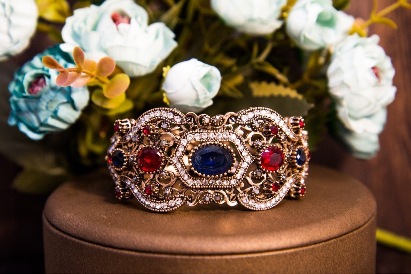 Широкий браслет из золотистого металла с декором из разноцветных кристаллов.