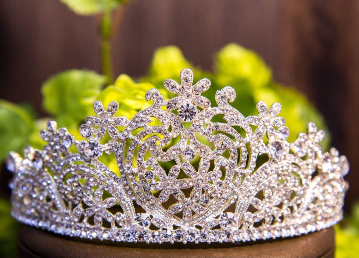 Золотистая корона для прически невесты, покрытая россыпью прозрачных кристаллов.
