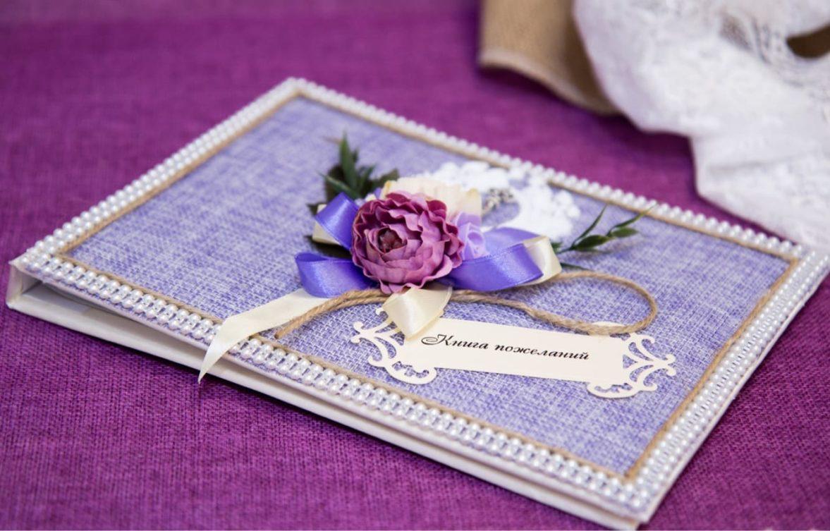 Изысканная книга для пожеланий, оформленная в фиолетовых тонах и украшенная бутонами.