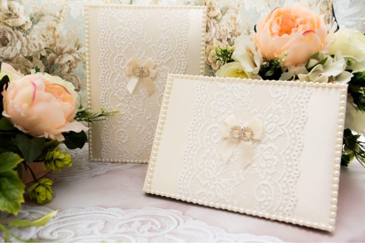 Кремовая книга для пожеланий, украшенная атласным бантом и белым кружевом.