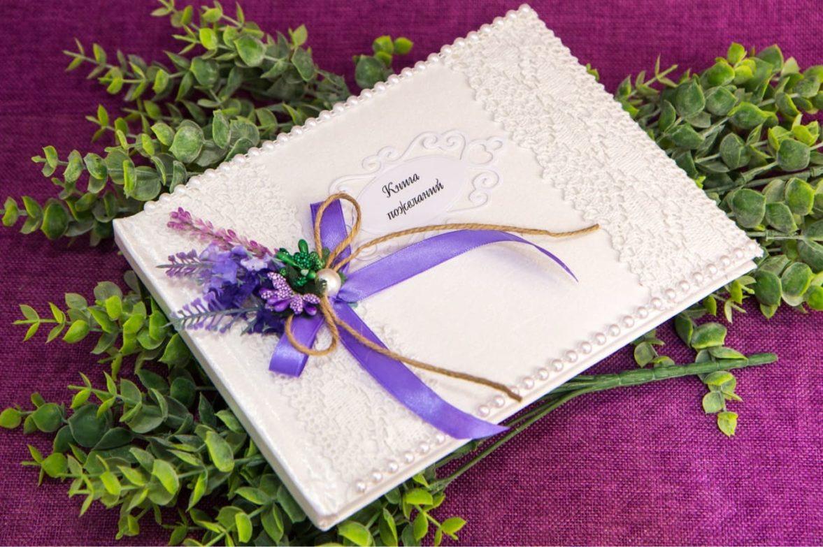 Изящная белая книга для пожеланий, оформленная бусинами и фиолетовым букетом.