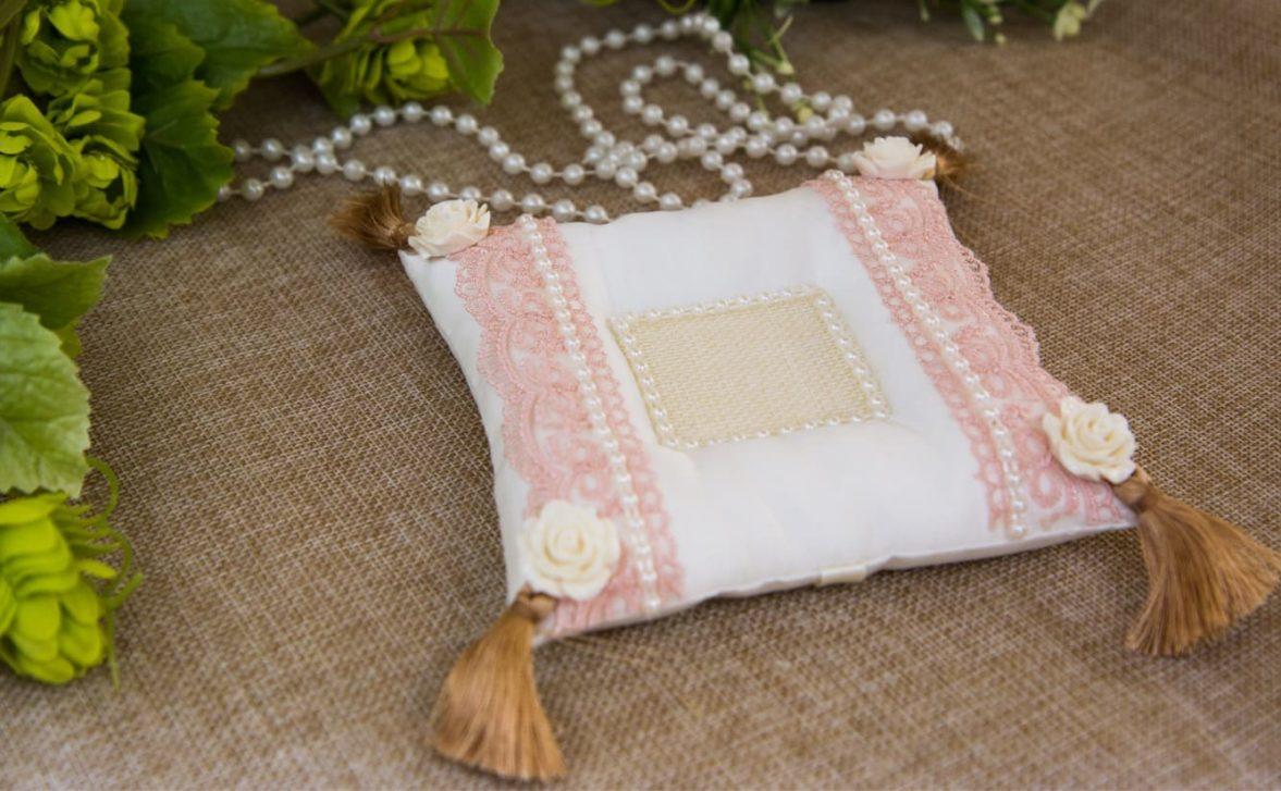 Элегантная подушечка для колец, украшенная кистями и тонким розовым кружевом.