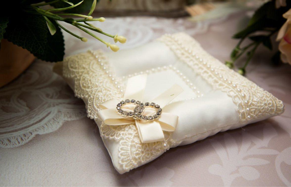 Бежевая подушечка для колец, украшенная кружевом и атласной ленточкой в тон.